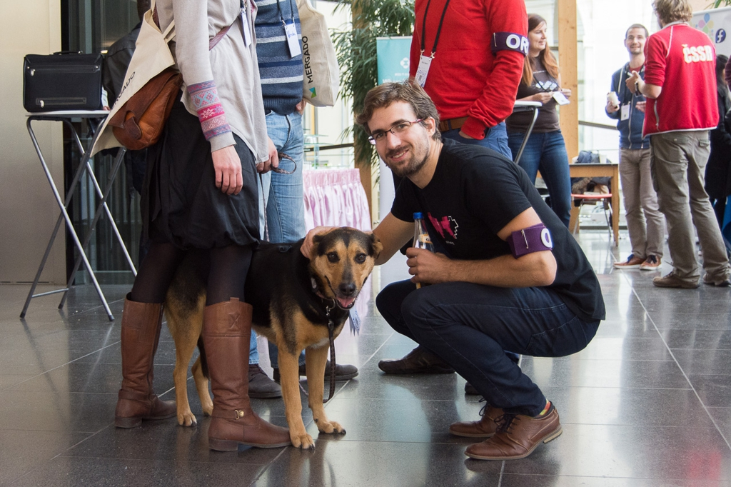 Tomáš Ehrlich smiling while petting a dog